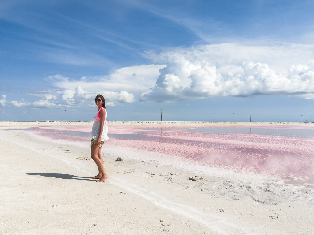 ragazza cammina sulla spiaggia davanti a laguna rosa