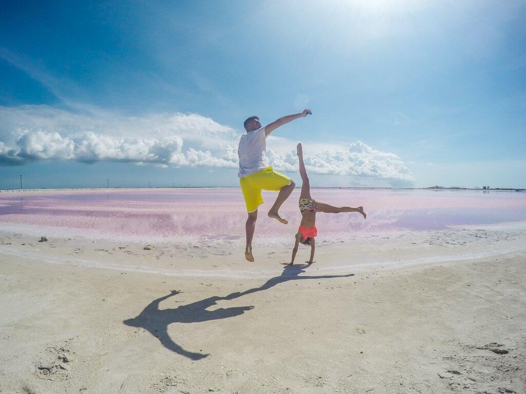 ragazzo e ragazza che fanno acrobazie davanti a laguna rosa di Las Coloradas